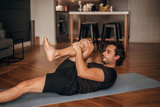 young fit man doing yoga on exercise mat at home