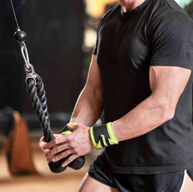 young fit muscular man close up doing triceps pull down rope extension exercise in modern fitness center