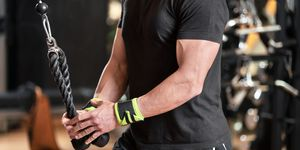 Young fit muscular man close up doing triceps pull down rope extension exercise in modern fitness center.