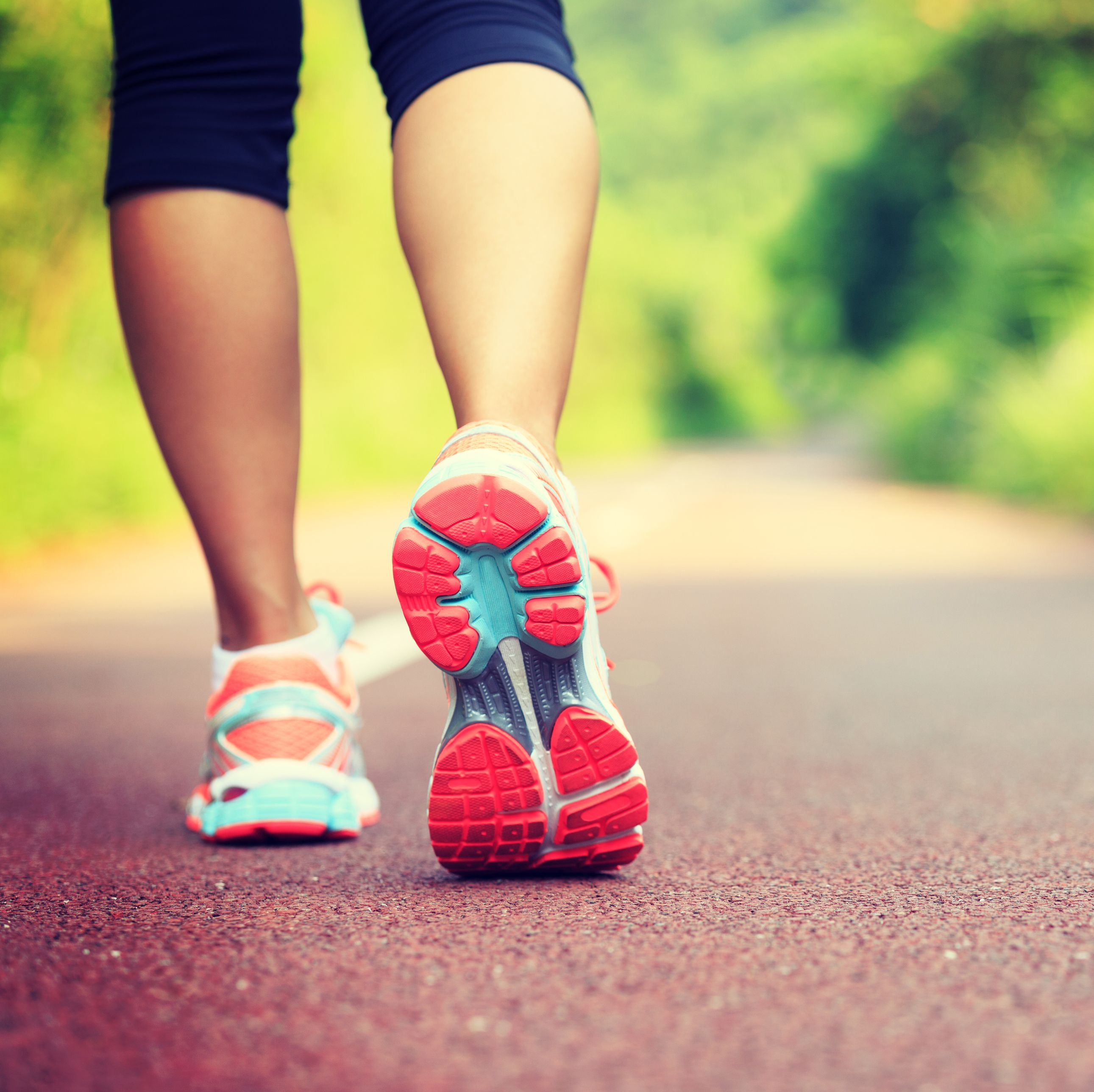 Young fitness female runner legs ready for run on forest trail