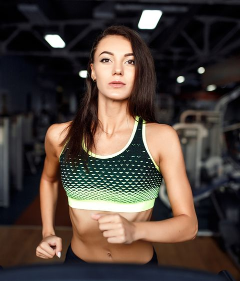 Young Fitness Woman Doing Cardio Exercises At The Gym Running On A Treadmill
