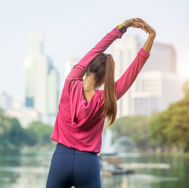 Young fitness woman runner stretching legs before run in the park