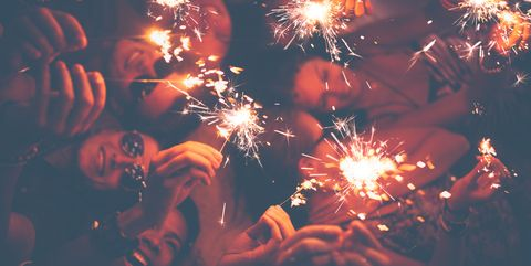 Young friends celebrating with sparklers at a beachparty