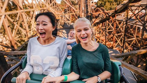 young friends riding roller coaster ride