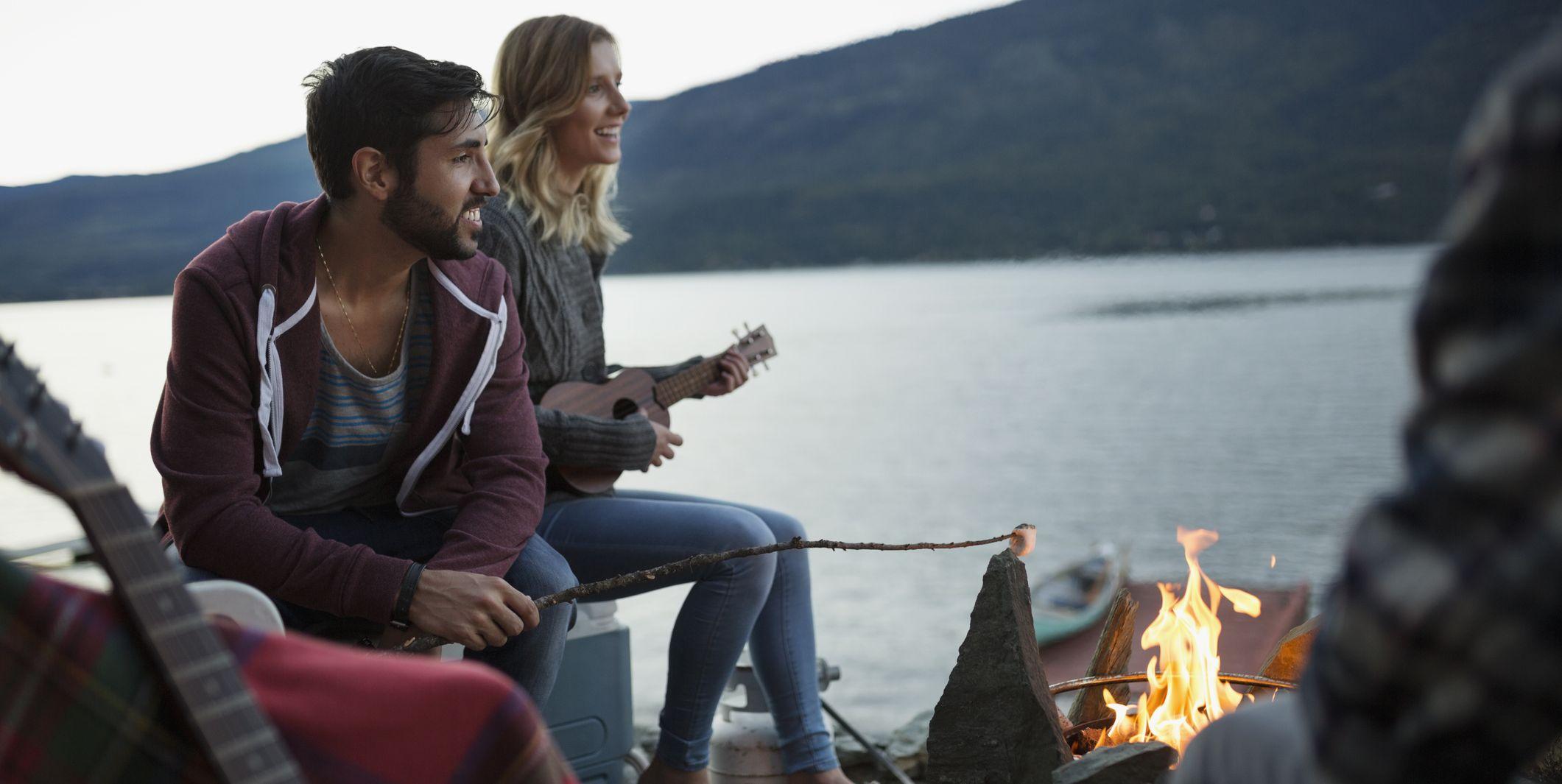 Young friends roasting marshmallows playing ukulele lakeside campfire