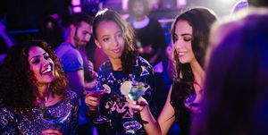 Young friends toasting with cocktails on night club party