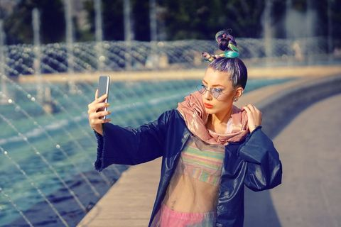 young funky fashion woman with trendy look taking selfie outdoors