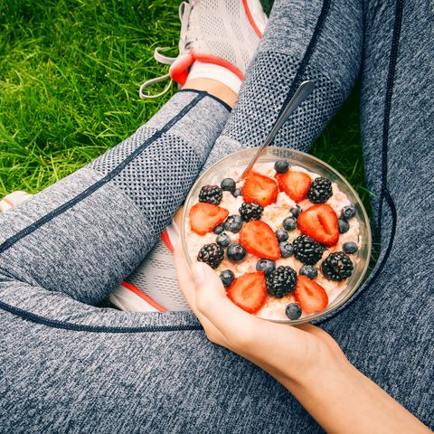 Young girl eating a oatmeal with berries after a workout .