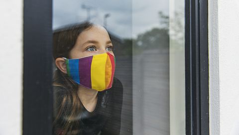 young girl in rainbow face mask looking through window