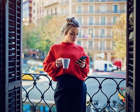 young girl is texting using her mobile phone at the balcony