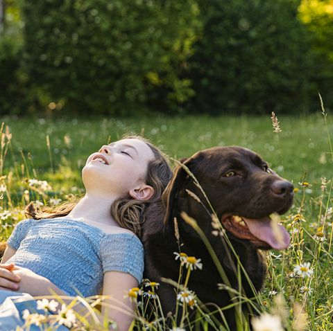 young girl leaning on her pet dog