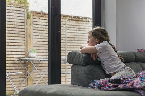 una niña mira por la ventana en un día de lluvia