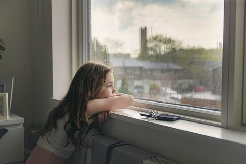 young girl looking out of window on a rainy day