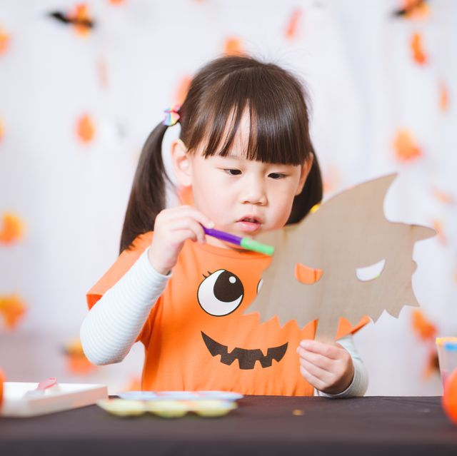 young girl painting witch mask for halloween party at home