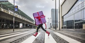 Young girl running with large gift on street