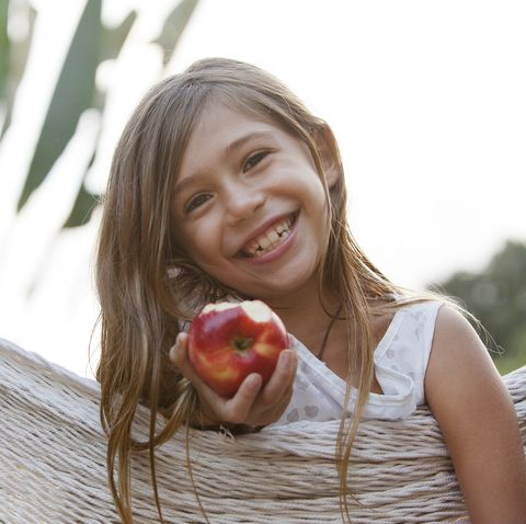 young girl smiling with bite out of a red apple