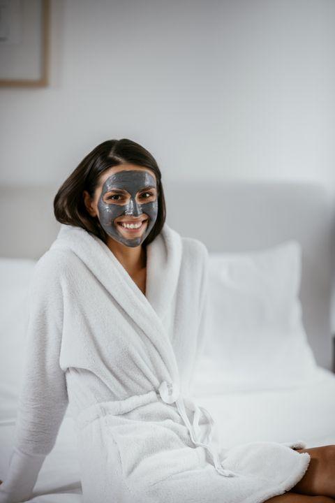una chica joven sonríe en albornoz con una mascarilla facial de color negro