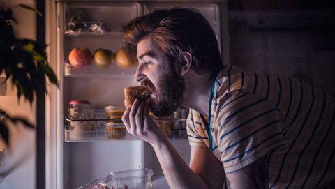 Jonge man eet 's avonds de koelkast leeg