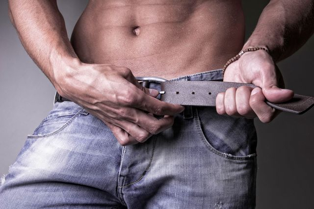 young handsome man undoing his belt and jeans