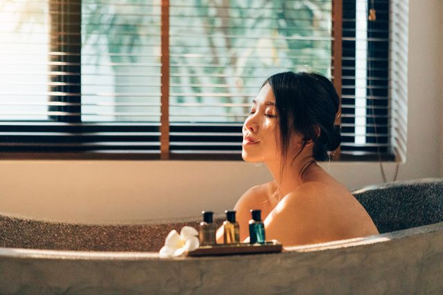 staycation young happy woman enjoying in bubble bath in hotel bathroom with her eyes closed