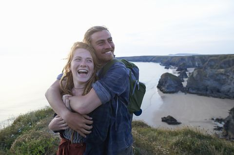 Young hiking couple embracing and laughing on Atlantic coastline.
