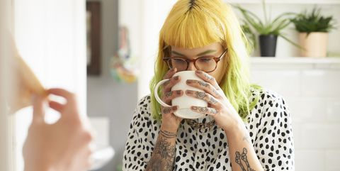 Young hipster woman drinking from a mug in her kitchen