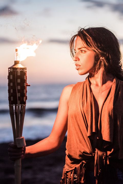 Young hipster woman holding a torch on the beach.
