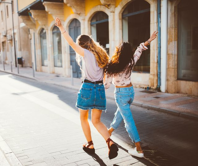 young hipster women on holidays walking cheerfully in old streets