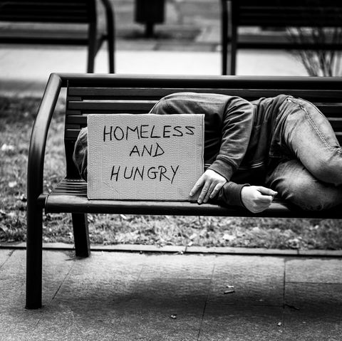 Young Homeless Depressed Man Lying Down on Bench