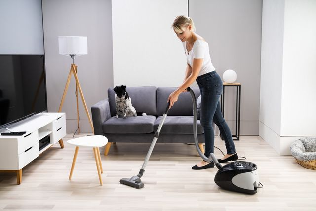 young maid cleaning carpet with vacuum cleaner