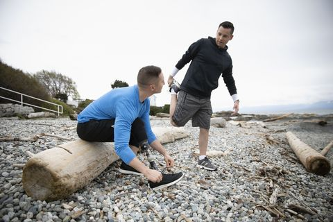 Young male amputee tying shoe on beach, talking with boyfriend