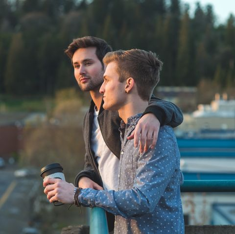 Young male couple watching the sunset from a city balcony