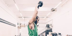 Young male cross trainer weightlifting kettlebell in gym