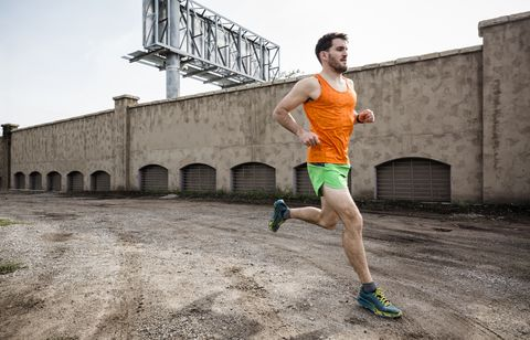 Young male runner running on urban wasteland
