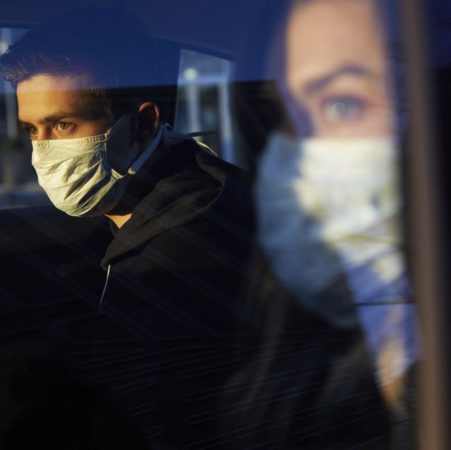 young man and woman in car wearing a virus protective face masks
