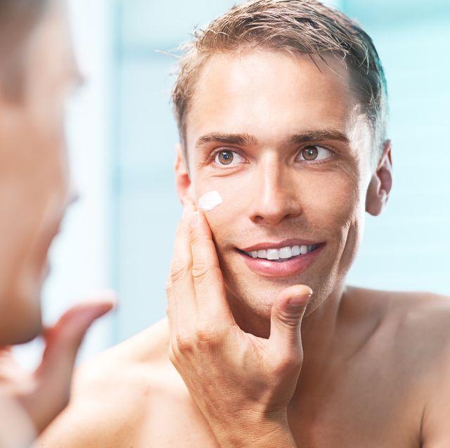 hombre echándose crema hidratante en la cara