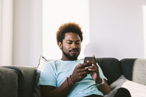 young man at home reading messages on smart phone