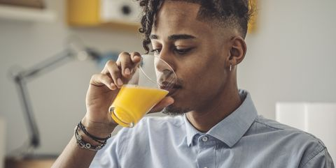 man met hip kapseldrinkt sinaasappelsap in blouse.