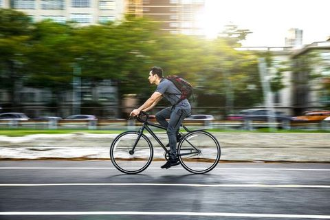 Young man cycling in the city, commuting to work