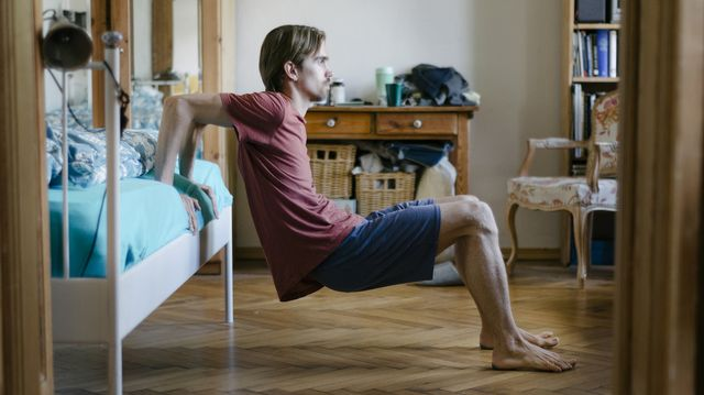 young man doing body weight exercises at home