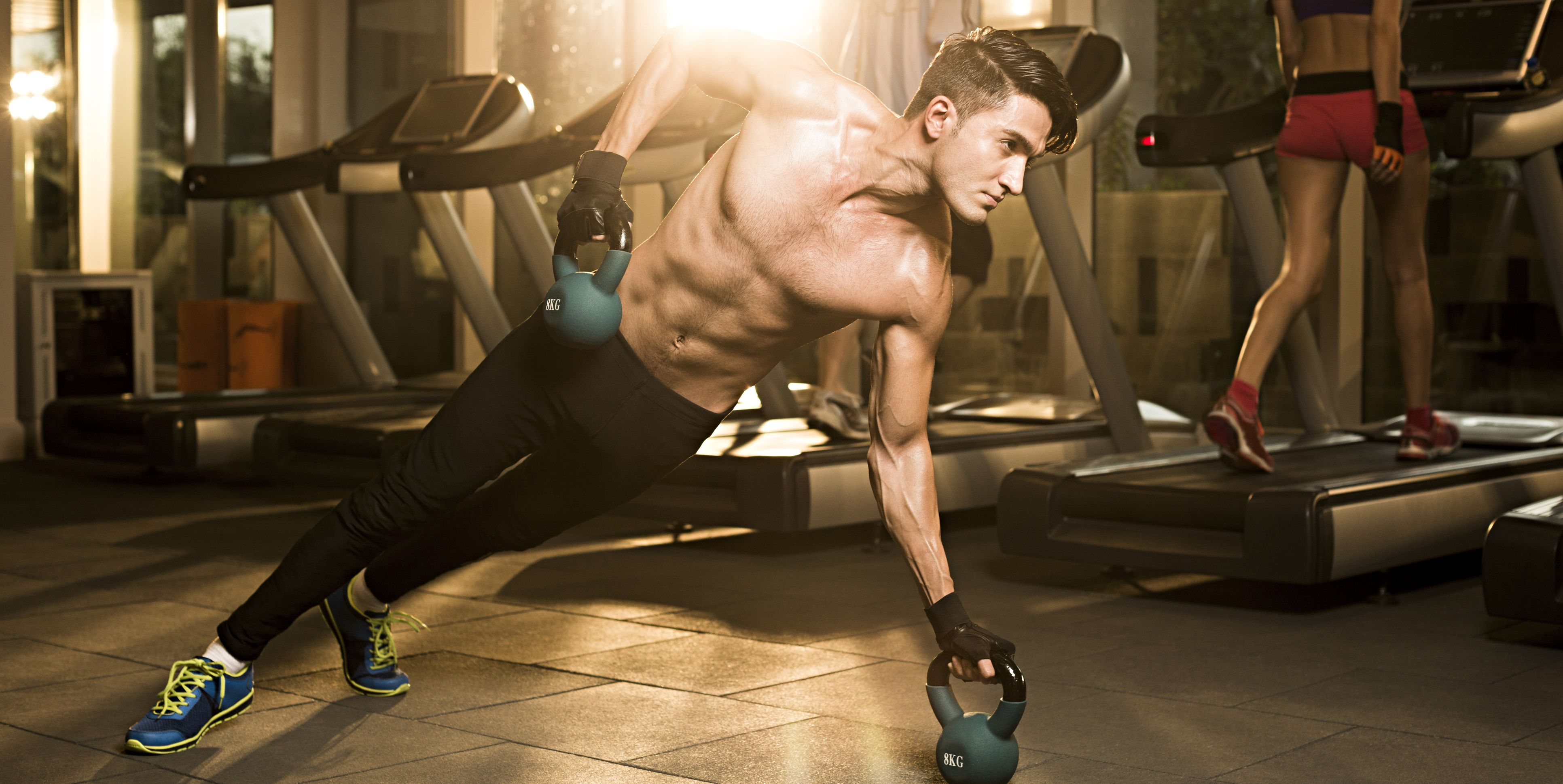 Young man doing kettlebell in gym