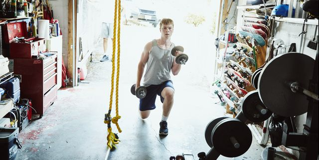young man doing lunges with dumbbells in gym in garage