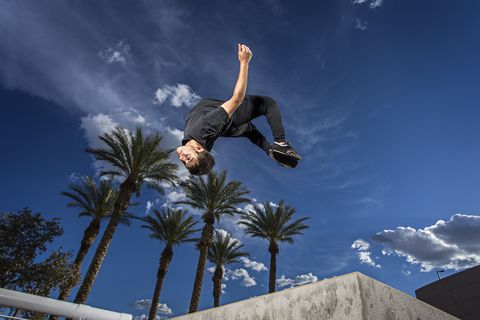 Young man doing parkour jump in the city, flipping.