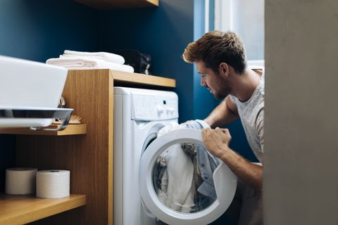 young man doing the laundry at home