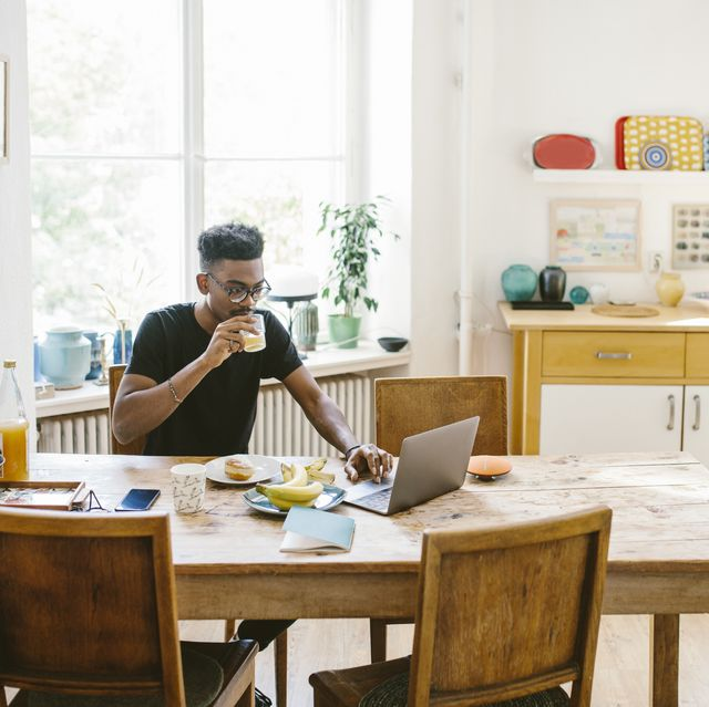 young man drinking juice while using laptop at table in house