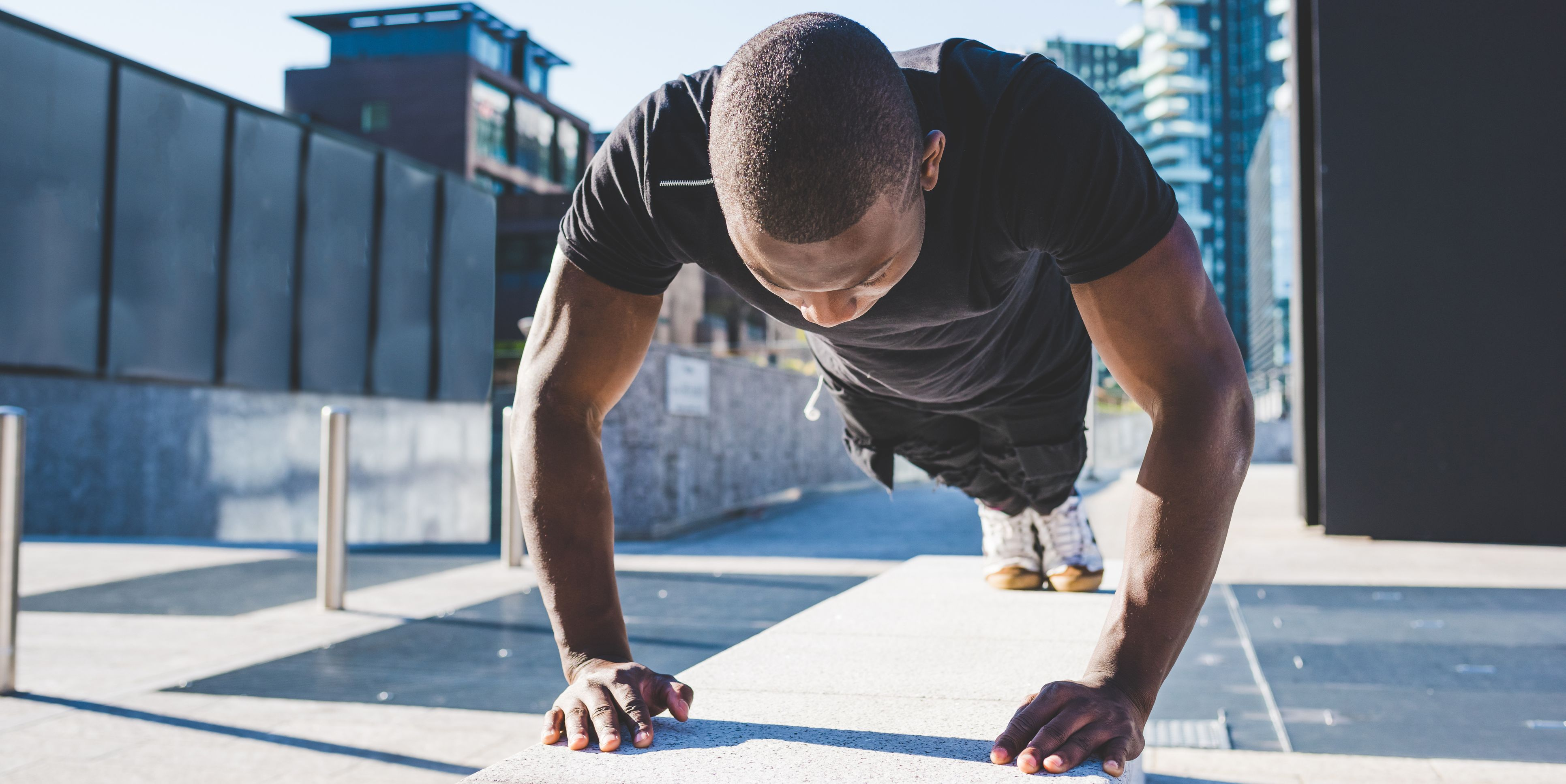 Young man exercising outdoors, doing push-ups