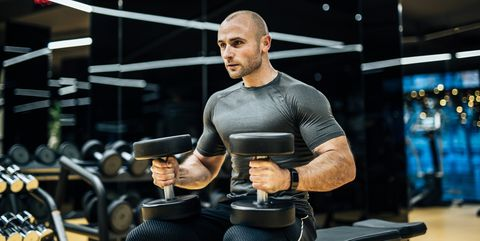 Young man exercising with weights in the local gym