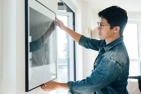 young man hanging picture on wall at home