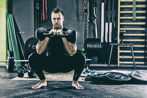 Young Man Holding Kettlebell While Exercising At Gym