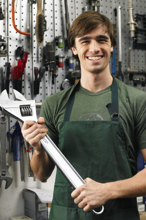 Young man holding large spanner, smiling, portrait